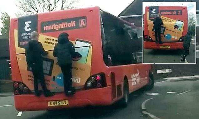 Moment schoolboys risk lives by clinging to the back of a moving bus