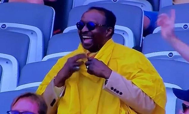 Hilarious moment cricket fan struggles to put on a yellow rain poncho