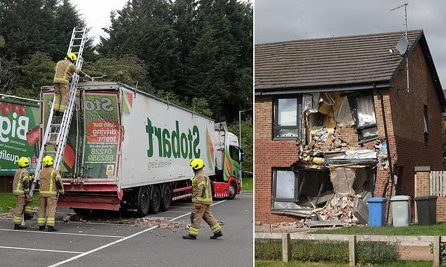 Family forced to flee in pyjamas as lorry is driven into their home